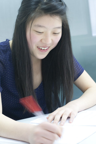 Student smiles as she corrects her paper