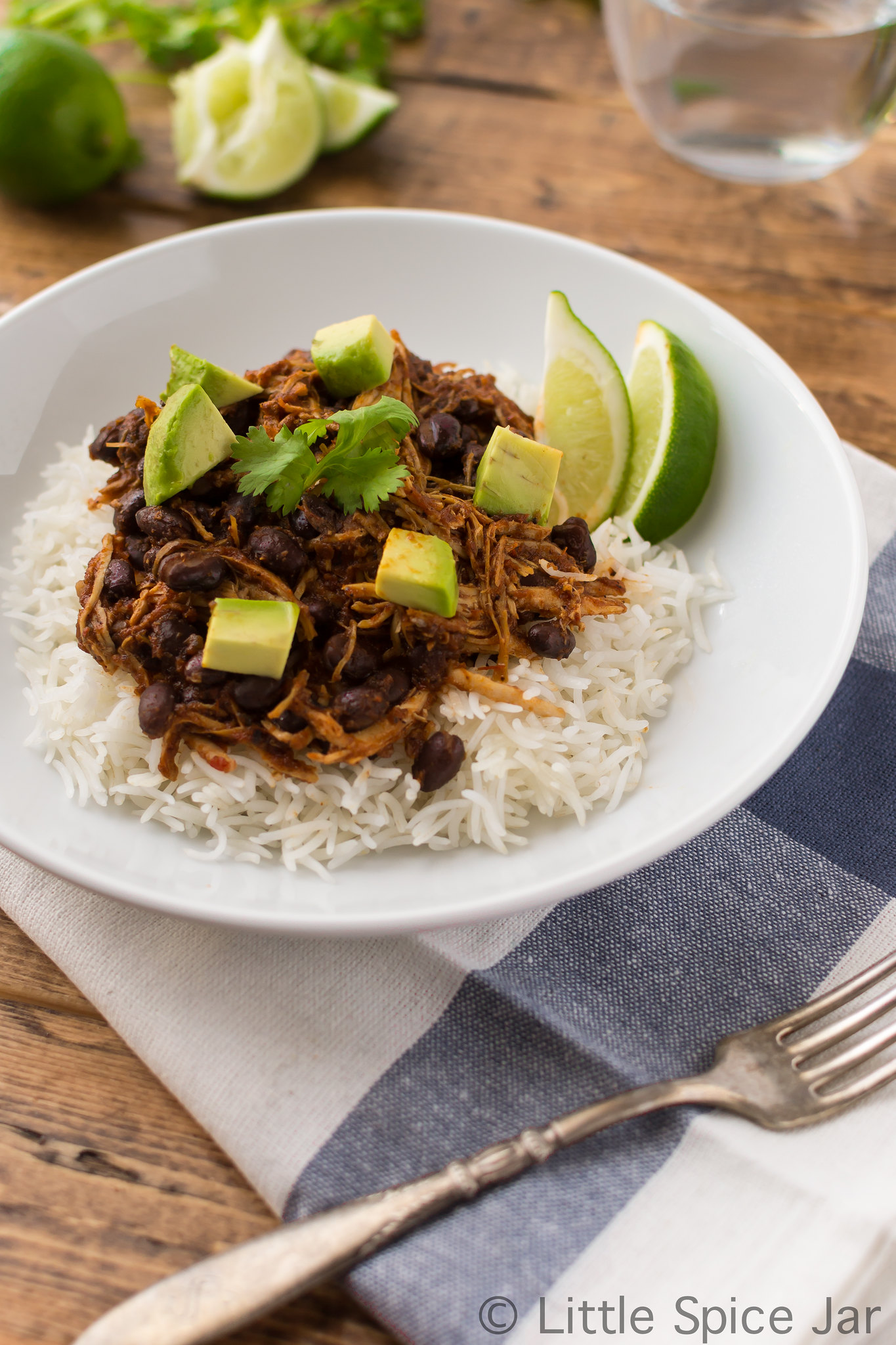 white rice topped with shredded chicken and black beans, diced tomatoes, and lime wedges