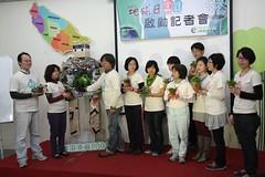 台灣環境資訊協會理事長陳建志(左3)與其他民間團體及夥伴,共同用小樹苗放入機器人的心中,呈現人心的轉變和行動的價值。(郭秉鋐 攝)
