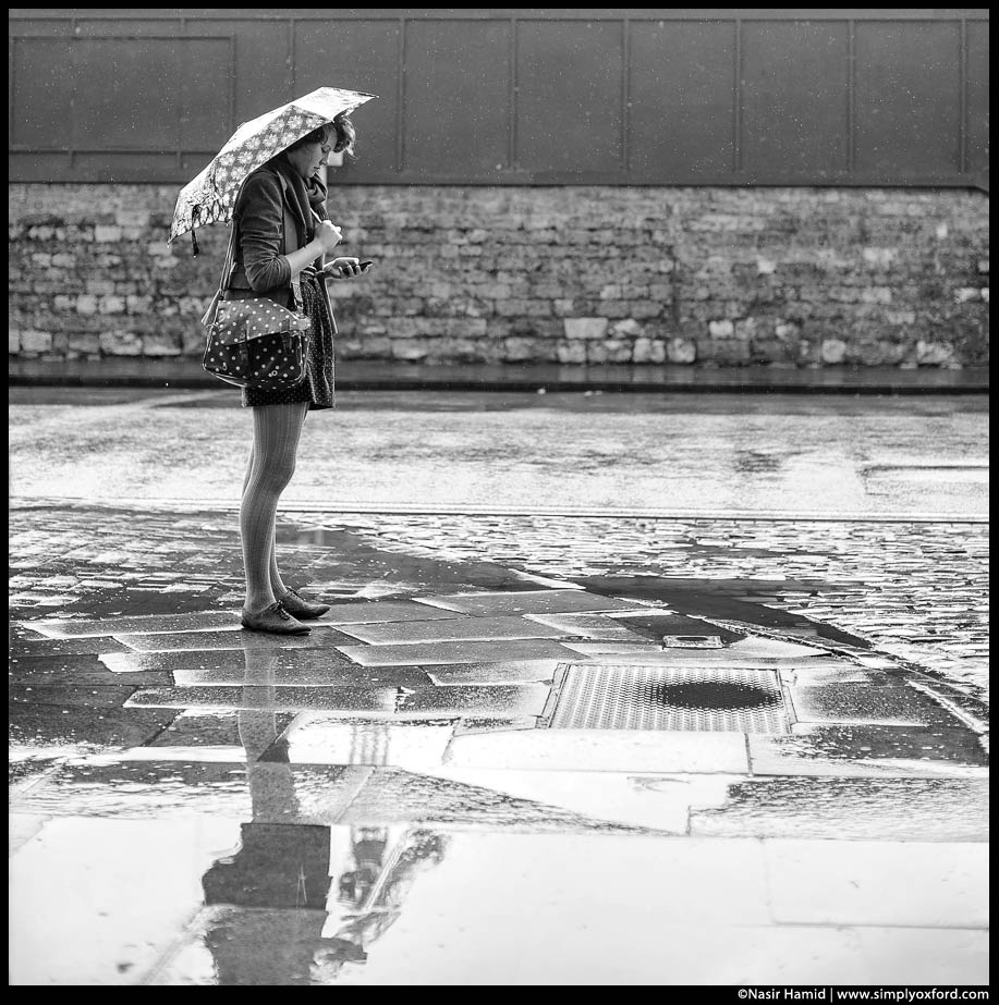 A girl standing in the rain holding an umbrella