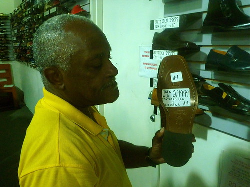 Mr. Alston shows us a pair of ostrich and lizard shoes at the Soul Train Suit Warehouse. Photo by Melanie Merz.