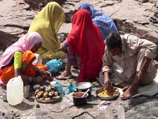 गाँव से बाहर खाना बनाते ग्रामीण