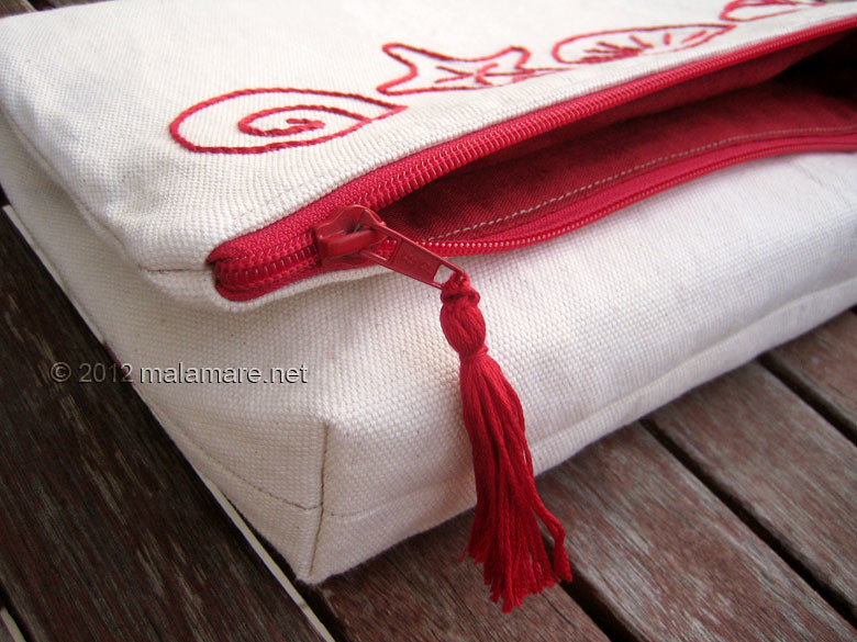 foldover cotton clutch with red hand embroidery zipper and tassel
