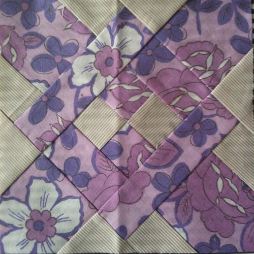 Dear Jane block made from purple vintage floral sheets and grey striped fabric
