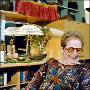 a vintage looking photo of eve sedgwick, wearing round brown glasses, and a colorful abstractly printed top, looking down to her left, and smiling