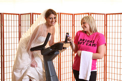 a bride in a white dress on a treadmill next to a woman wearing a pink shirt that says BRIDE BOOT CAMP
