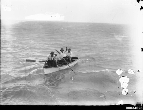 Four men in a rowing boat at sea, 1890-1953
