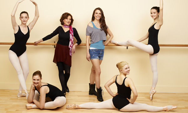 cast of bunheads in various ballet poses with the protagonist in the center wearing casual dancewear