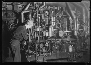 A Lynch bottle machine at work. In the center may be seen a blob of molten glass ready to drop into a mould, March 1937