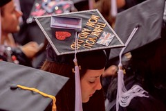 A student with a mortar board decorated in an international flavor looks over her program before U.S. Secretary of State John Kerry delivered the commencement address for Northeastern University's Class of 2016 on May 6, 2016, at TD Garden in Boston, Massachusetts. [State Department photo/ Public Domain]