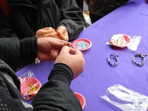 部落媽媽教導遊客串珠DIY。