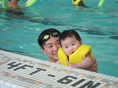 cute baby with her dad in the pool