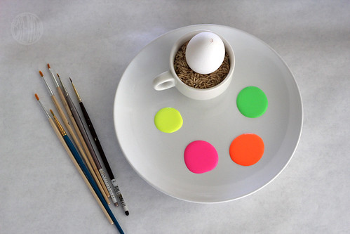 neon paint on a plate with paintbrushes and an egg for painting