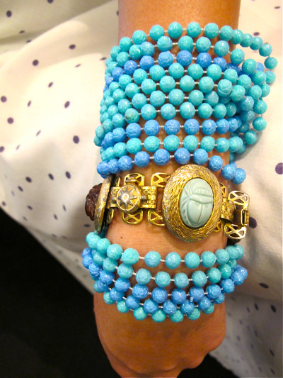 Here, we've looped a multi-strand necklace round and round the wrist and matched it with a beaded medallion bracelet that pops right in the middle of all that turquoise!