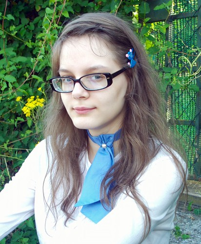 Jabot bleu sur blouse blanche à plastron.