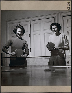 """Two young women, members of the Ottawa """"Knick-Knack"""" club, a Canadian Welfare Club, play ping-pong / Deux jeunes femmes, membres du club « Knick-Knack » d'Ottawa, un club d'assistance canadien, jouant au ping-pong"""