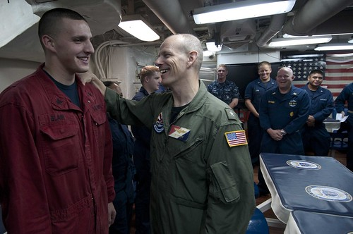 Commander, Task Force 70 Rear Adm. John R. Haley speaks with Damage Controlman 3rd Class Steven Blair