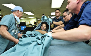 Medical staff move a patient in an ICU.