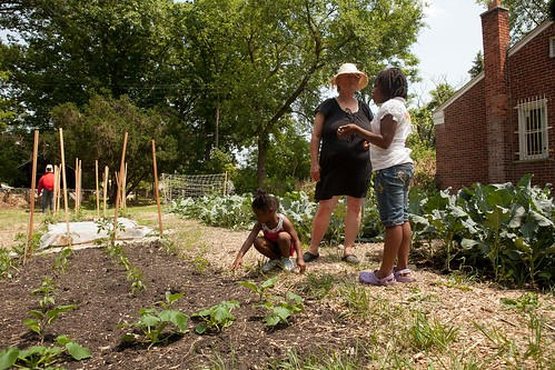 Riet Schumack and Jessica Easterleing, 9, talk about the Farmway while Ondrea Bryant, 3, checks her vegetables.