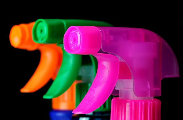 tre prodotti spray per le pulizie, uno di colore arancione, uno fucsia e uno verde