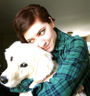 A picture of me with my pup. She's giving puppy eyes to the camera. I am looking at her and wearing a green plaid shirt.