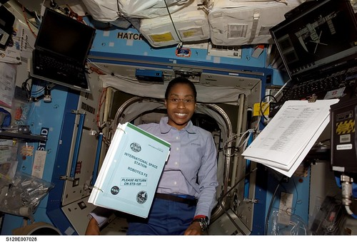 Posing for a photo as a procedures handbook floats freely nearby in the Destiny laboratory of the International Space Station.