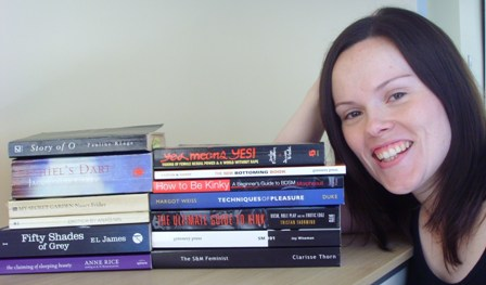 Catherine next to a stack of BDSM books