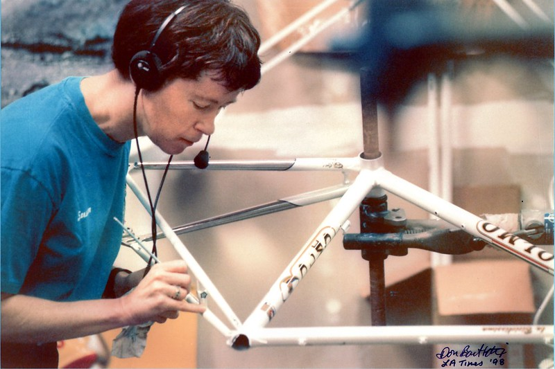 Susan Cunningham on the phone while striping at vintage bicycle frame.