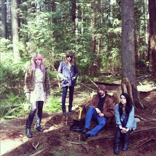 the members of White Lung standing in a forest