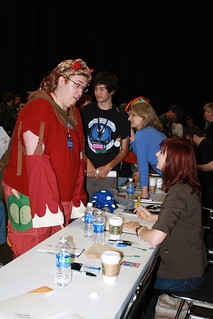 a male fan dressed as a pony talks to Lauren Faust