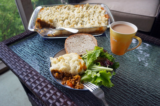 A vertically composed photograph with the angled shepherd's pie centered in the background, and a plate of shepherd's pie with bread and salad centered just in front of it. A yellow and orange mug, which reads 'tea', breaks the neat composition slightly, sitting between them with its handle jutting out to the right.