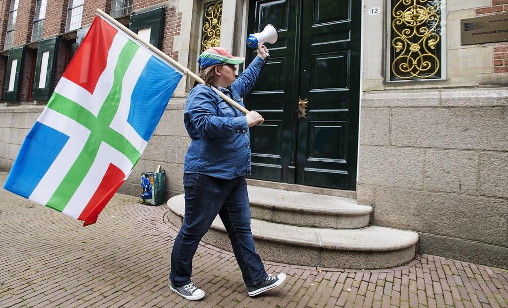 Man protesteert met Groninger vlag bij het provinciehuis.
