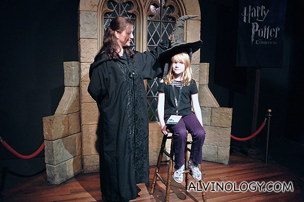 A young girl getting the sorting hat placed on her