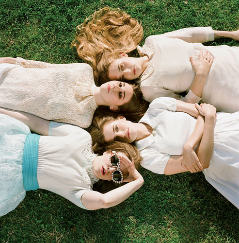 the four leads of Girls posed lying on the grass wearing pretty dresses