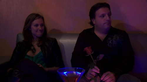 A woman and a man sit on a couch in a dimly lit room. They both look at something out of the frame, toward the right of the frame. The man holds a rose in his hands. A full martini glass sits between them.