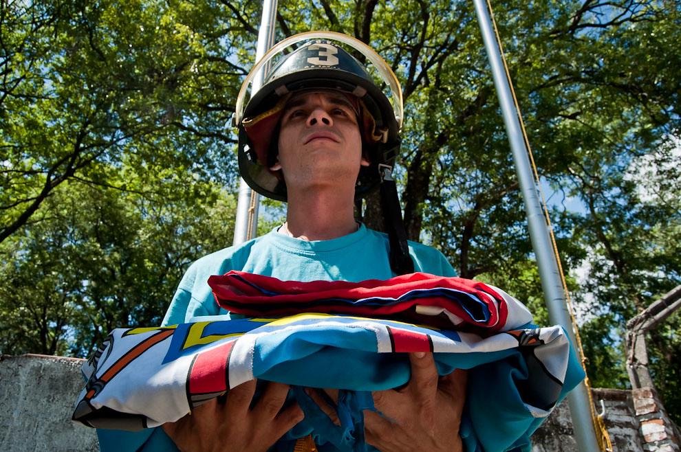 Un bombero combatiente de la Tercera Compañía sostiene las dos banderas, de la Institución y de la Patria, que serán izadas en lo alto del cuartel durante la formación y el comienzo del entrenamiento de los sábados. Posteriormente las banderas son arriadas al culminar las prácticas al caer la noche. (Elton Núñez)