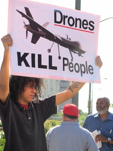 Abayomi Azikiwe in background as Jeremy holds sign at demonstration in solidarity with the people of Syria on June 27, 2012 in downtown Detroit. Demonstrations are taking place across the country in opposition to US war threats against Syria. by Pan-African News Wire File Photos