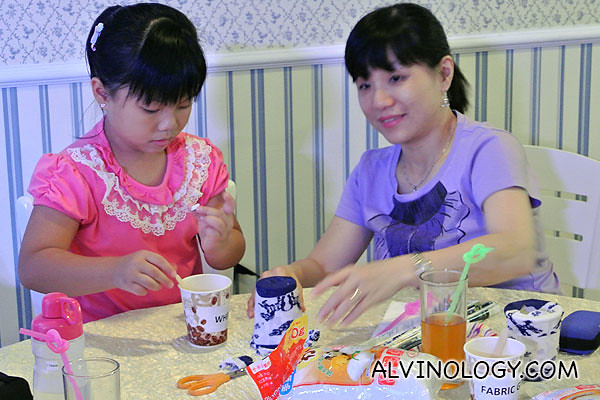 A mother helping her daughter with the glue
