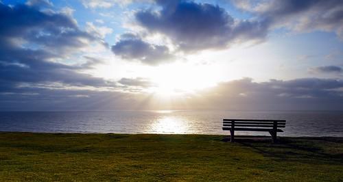 ocean light sunset sea sky cloud sun reflection grass wales bench nikon explore 1224 southerndown flickrexplore d300s bestcapturesaoi mygearandme mygearandmepremium mygearandmebronze mygearandmesilver