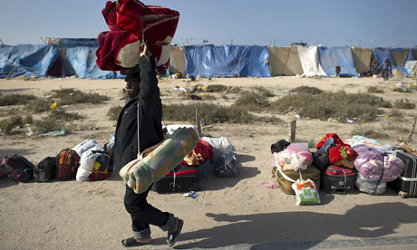 African migrant carries his belongings at a makeshift camp in Libya. Three Africans were murdered by counter-revolutionary rebels on August 24, 2012. by Pan-African News Wire File Photos