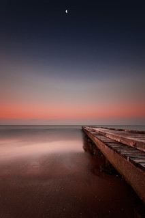 The pier, the sea and the moon at sunrise