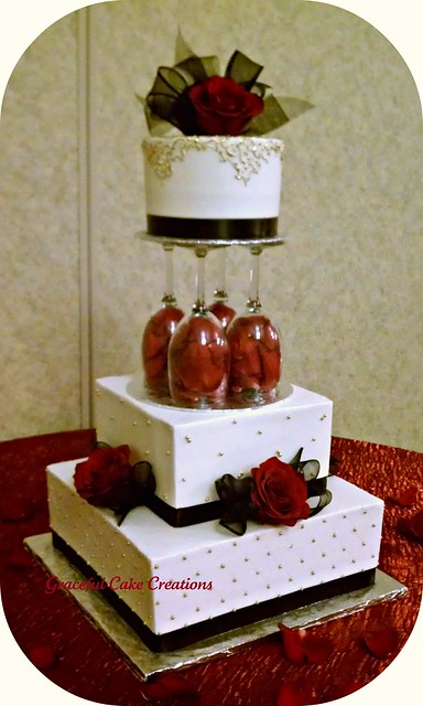 Elegant Ivory Wedding Cake with Gold Black and Red accents