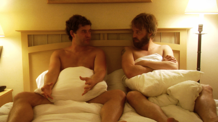 Two men sit in bed together, facing each other. They are naked and pillows cover most of their bodies. Lamps are lit on either side of them.