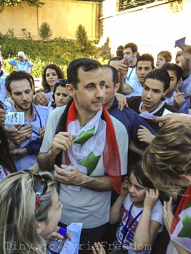 Bashar Assad, informal, with supporters and a Syrian flag around his neck