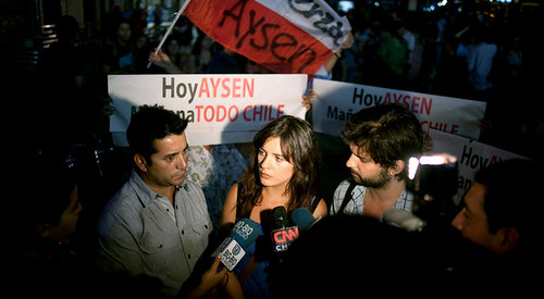 Vallejo, a young woman, stands in a crowd of television journalists