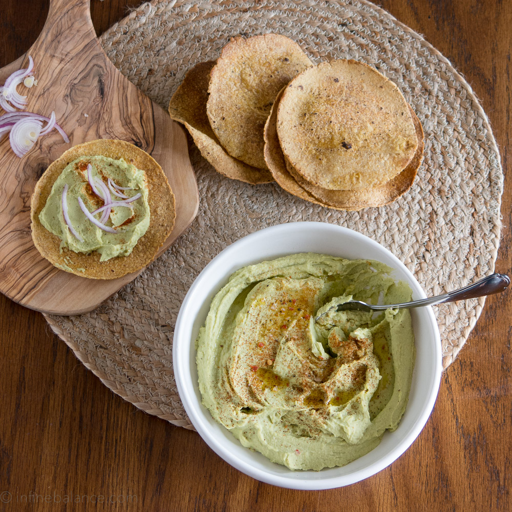 bissara spread in a white bowl served with crispy flat breads and red onions