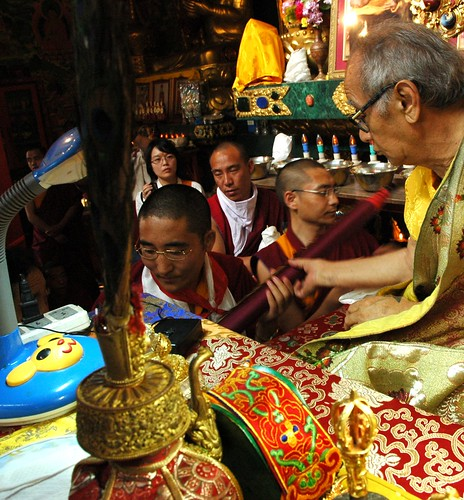 His Holiness Jigdal Dagchen Sakya recieves a rolled up Thangka from a monk during mandala offering, more monks and students wait in line, lama's table fine objects, silks, Sakya Lamdre, Tharlam Monastery of Tibetan Buddhism, Boudha, Kathmandu, Nepal by Wonderlane
