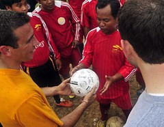 SIHANOUKVILLE, Cambodia (July 28, 2012) Lt. j.g. Adam Cohen hands over a signed soccer ball to the captain of a local Cambodian soccer team in Sihanoukville during a community service project during Pacific Partnership 2012, 28 July. (Photo by Kristopher Radder)