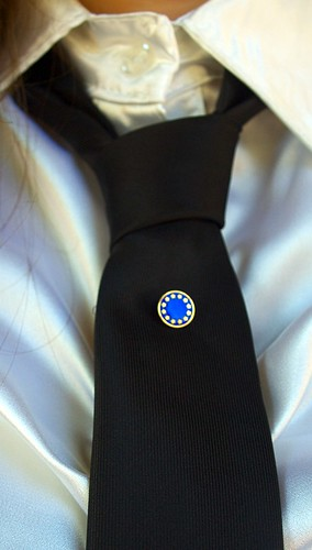 Thin black tie with a blue and gold tie pin representing the European Union's logo.