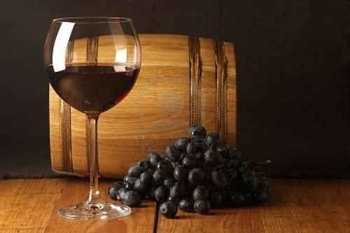 7255389-copa-de-vino-oscuro-uva-y-souvenirs-crianza-en-madera-de-superficie